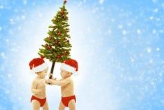 圣诞节婴孩哄骗当前Xmas树,儿童圣诞老人帽子 免版税图库摄影