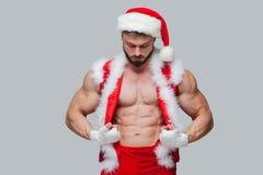 圣诞节 性感的圣诞老人 戴圣诞老人帽子的年轻肌肉人展示他的肌肉 肌肉的战斗机 库存图片
