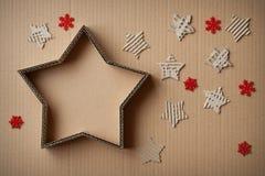 圣诞节以星的形式礼物盒,围拢由装饰,在纸板背景 免版税库存照片