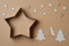 圣诞节以星的形式礼物盒,围拢由装饰,在纸板背景 免版税图库摄影