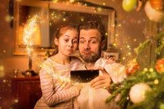 圣诞节-父亲和女儿作为` selfie在电话的`照片 免版税库存照片