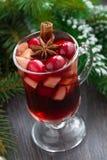 圣诞节仔细考虑了在一块玻璃的酒在木背景 免版税图库摄影