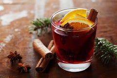 圣诞节仔细考虑了酒或gluhwein用香料和橙色切片在土气桌,传统饮料上寒假,不可思议的光 免版税库存照片