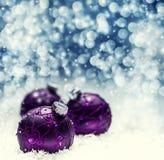 圣诞节紫色球下雪并且间隔抽象背景 与bokeh defocused光的欢乐圣诞节摘要背景 免版税库存照片