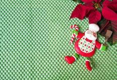 圣诞节-绿色背景,一品红,橙色和滑稽的厨师圣诞老人 免版税图库摄影