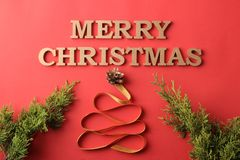 圣诞节 节假日 与一棵装饰圣诞树的圣诞节构成和在一红色backgroun的题字圣诞快乐 库存图片