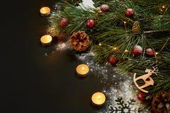 圣诞节 Xmas玩具、灼烧的蜡烛和云杉的分支在黑背景顶视图 文本的空间 免版税库存照片
