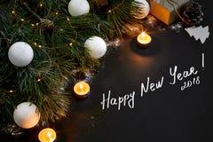 圣诞节 Xmas玩具、灼烧的蜡烛和云杉的分支在黑背景顶视图 文本的空间 免版税库存图片