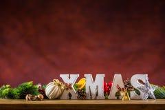 圣诞节 Xmas词由木信件做成在一张木板桌 圣诞节球杉木锥体星作为装饰的冷杉枝杈 图库摄影
