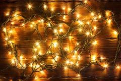 圣诞节bokeh背景 在一张棕色木桌上的发光的金黄诗歌选 库存照片