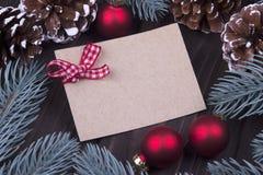 圣诞节Xmas新年假日与空的纸板圣诞节球响铃丝带冷杉分支锥体的贺卡概念在黑暗 免版税库存图片