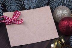 圣诞节Xmas新年假日与空的纸板圣诞节球响铃丝带冷杉的贺卡概念在黑暗木分支 库存图片