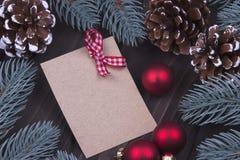圣诞节Xmas新年假日与空的纸板红色圣诞节球丝带冷杉的贺卡概念在黑暗木分支 免版税库存图片