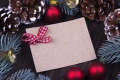 圣诞节Xmas新年假日与空的纸板红色圣诞节球响铃丝带冷杉分支锥体的贺卡概念在d 免版税库存图片