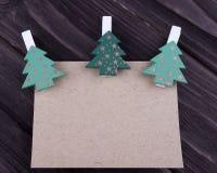 圣诞节Xmas新年假日与纸板三在晒衣夹的圣诞树emty板料的贺卡概念在黑暗求爱 库存图片