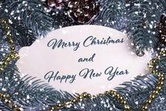 圣诞节Xmas新年假日贺卡木牍文本快活的Chrismas和新年快乐冷杉分支锥体金necklac 库存照片