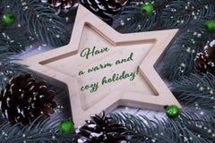 圣诞节Xmas新年假日贺卡用木五个指向的星冷杉分支锥体绿色莓果和文本有一温暖 免版税库存图片