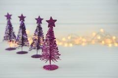 圣诞节xmas装饰桃红色紫色闪烁xmas树和光的摄影图象有白色木背景 图库摄影