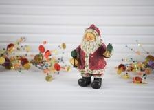 圣诞节xmas装饰闪耀的圣诞老人装饰品的摄影图象有在白色木头的欢乐金子xmas背景 免版税库存照片