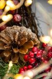 圣诞装饰和光围拢的杉木锥体 库存照片