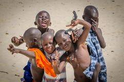 圣路易斯,塞内加尔- 2013年10月20日:朋友小组画象获得未认出的非洲的男孩摆在和乐趣 免版税库存照片