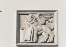圣马克` s在利沃夫州,乌克兰飞过了与一本书的狮子在老房子墙壁上 库存照片