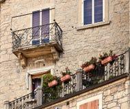 圣马力诺,圣马力诺- 2017年7月10日:一个石房子的设计有窗口和阳台的 免版税库存照片