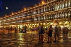 圣马可广场,威尼斯,意大利,被照亮在与许多的晚上无法认出的人民、五颜六色的天空和满月 库存图片