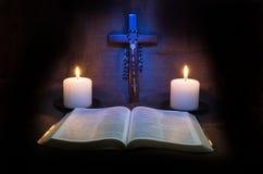 圣经、念珠、耶稣受难象和两个蜡烛 免版税图库摄影