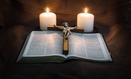 圣经、耶稣受难象和两个蜡烛 库存照片