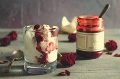 圣代冰淇淋冰淇凌用在巧克力顶部的樱桃和在黑暗的背景的干玫瑰色花 爱,华伦泰` s天 免版税库存图片