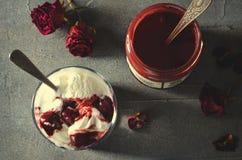 圣代冰淇淋冰淇凌用在巧克力顶部的樱桃和在黑暗的背景的干玫瑰色花 爱,华伦泰` s天 免版税图库摄影