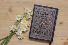圣洁古兰经书和黄水仙在木背景 ramadan 库存照片