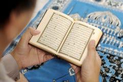 读圣洁古兰经的年轻人 免版税库存图片