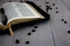 圣经和咖啡在木板 免版税库存图片