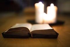 圣经在木地板,灼烧的蜡烛在背景中放置了 免版税库存照片