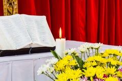 圣经开放在与蜡烛的一张桌上 免版税库存图片