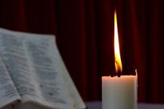 圣经开放在与蜡烛的一张桌上 库存照片