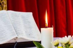圣经开放在与蜡烛的一张桌上 免版税库存照片