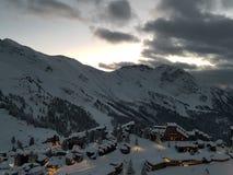 在一下雪的山villlage的冬天日落 图库摄影