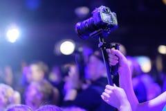在一个三脚架的一台照相机在摄影师的手上 库存照片