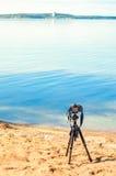 在一个三脚架的一台照相机在海背景 免版税库存照片