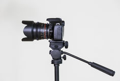 在一个三脚架的数字式SLR照相机有在灰色背景的一个可移动的手工透镜的 在内部的射击 图库摄影
