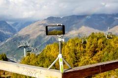 在一个三脚架的智能手机在山、一种推力和一条彩虹在背景 免版税库存图片