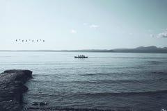 在一个不可思议的湖的孤零零独木舟航行在晚上点燃 免版税库存图片