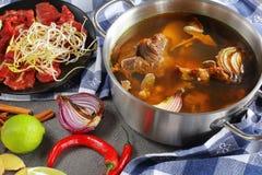 在一个不锈的平底锅的热的牛肉骨头汤 图库摄影