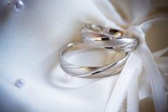 在一个丝绸背景的婚戒 免版税库存图片
