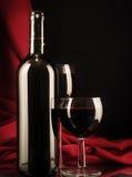 在一个丝绸背景的红葡萄酒玻璃和瓶 免版税库存照片