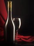 在一个丝绸背景的红葡萄酒玻璃和瓶 免版税库存图片