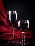 在一个丝绸背景的红葡萄酒玻璃 库存照片